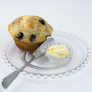 Blueberry muffin made with classic homestyle muffin mix on clear glass plate with knife and small dish of butter.