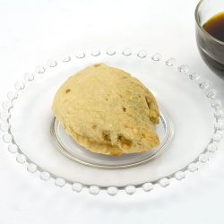 Butter brickle scone made with butter brickle scone mix sitting on a clear glass plate. There is a cut of coffee just off to the side of the plate.