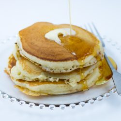 Stack of Buttermilk Pancakes made with buttermilk pancake mix with melting butter and syrup dripping down the stack. Fork sitting next to pancakes on clear glass plate.