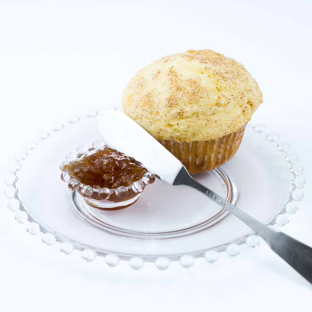 Muffin baked with Classic Homestyle Muffin Mix sitting on clear glass plate with spreading knife and dish of jam
