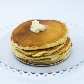 Short stack of cornmeal pancakes made with cornmeal pancake mix with melting butter on top, sitting on clear glass plate.