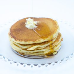 Short stack of cornmeal pancakes made with cornmeal pancake mix with melting butter and syrup being poured onto stack, sitting on glass plate.