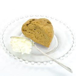 Gingerbread Scone made with Gingerbread Scone Mix. The scone is sitting on a clear glass plate; the plate also has a dollop of Devonshire cream and a knife--just ready for someone to split the scone and spread this on the scone prior to eating.
