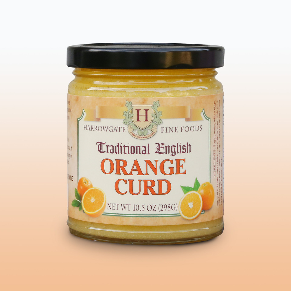 A glass jar with a black cap filled with Orange Curd. The label states it is made by Harrowgate Fine Foods, and is Traditional English Orange curd.