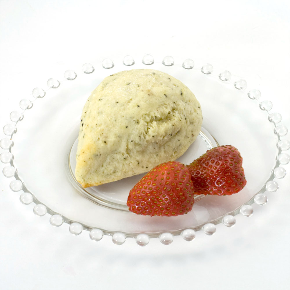 Indian Chai Scone made with Indian Chai Scone Mix; the scone is sitting on a clear glass plate, and the plate is garnished with fresh strawberries.