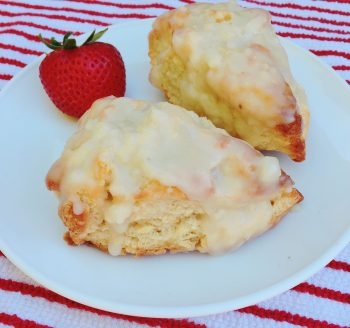 Two lemon-ginger scones, glazed and on plate with fresh strawberry. Created from Original Recipe Scone Mix.