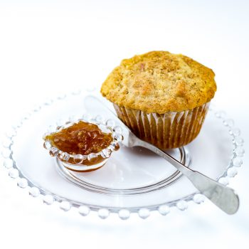Freshly baked Oatmeal Muffin made with Oatmeal Muffin Mix witting on glass plate with small dish of jam and a spreading knife.