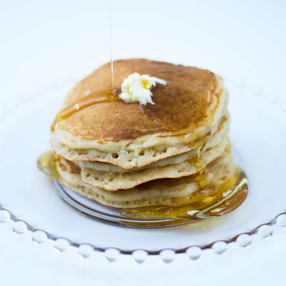 Short stack of Oatmeal Pancakes made with Oatmeal Pancake Mix with melting butter, and syrup being poured on, on glass plate.