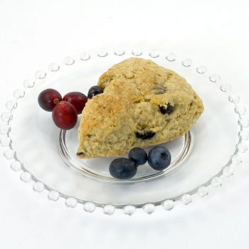 Blueberry-Oatmeal scone made with Original Oatmeal Scone Mix. The scone is sitting on a clear glass plate, and the plate is garnished with blueberries and fresh cranberries.