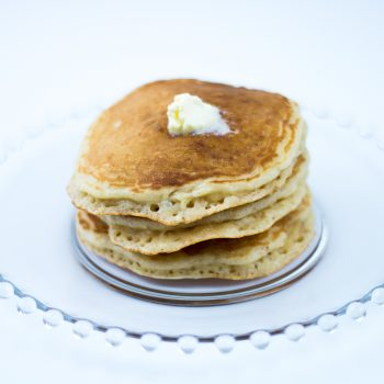 Short stack of atmeal pancakes made with oatmeal pancake mix with pat of butter on top, on glass plate.