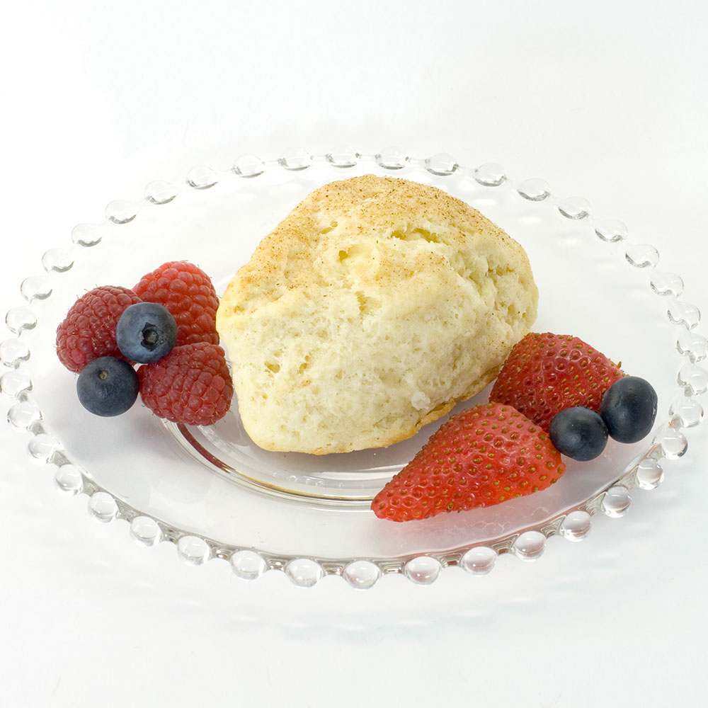 Plain scone made with Original Recipe Scone mix sitting on clear glass plate, garnished with raspberries, strawberries, and blueberries.