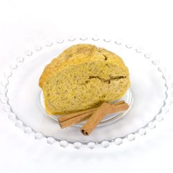 Pumpkin scone made with pumpkin spice Scone mix. Sitting on glass plate, with two cinnamon sticks garnishing the plate.