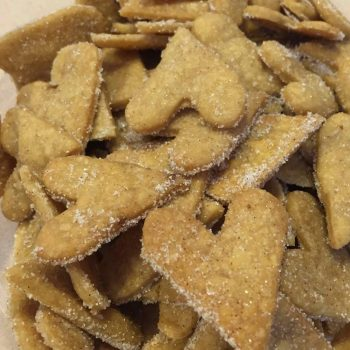 Dozens of thin, Baked heart-shaped shortbread cookie wafers sprinkled with cinnamon sugar.