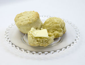 two southern style biscuits on clear glass plate, one cut open and spread with butter