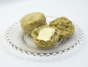 Two oatmeal biscuits on clear glass plate plate with one split open and buttered.