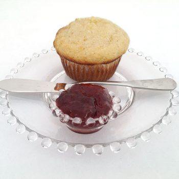 Cornmeal muffin made with VHS cornmeal muffin mix on glass plate with preserves in a small glass dish and a knife on the side of the plate