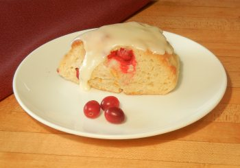Cranberry Orange Scone with Orange glaze, on plate with fresh cranberries. Created from Original Recipe Scone mix.